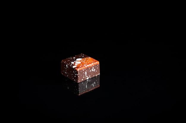 Caramelle di cioccolato del taglio variopinto di arte sul fuoco nero e selezionato