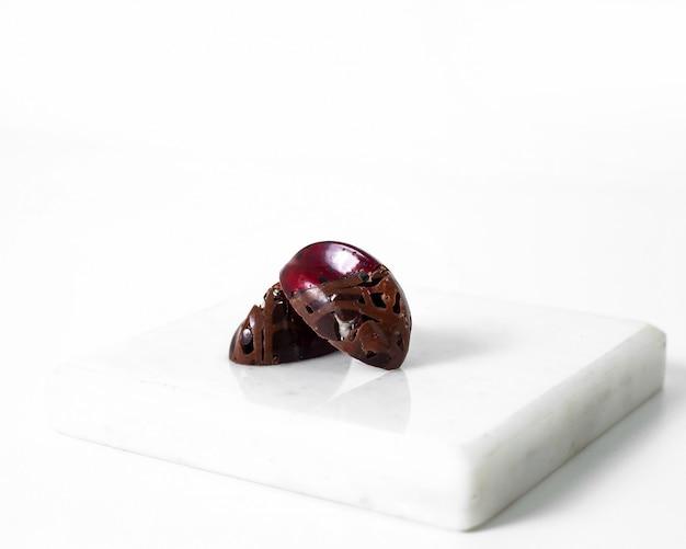 Caramelle di cioccolato disegnate pezzi di cioccolato marrone artistici sulla superficie bianca