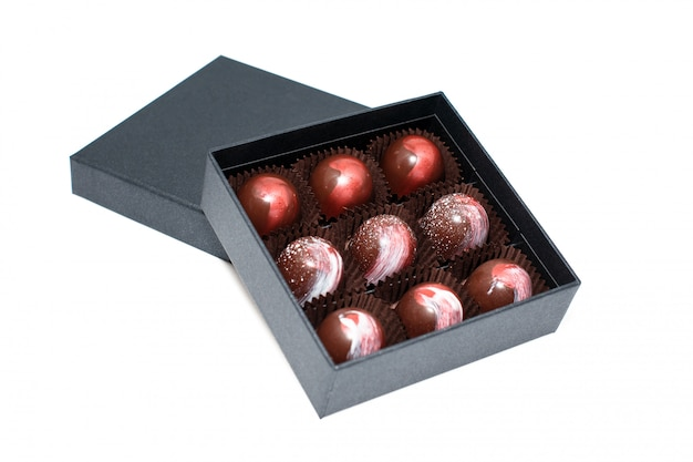 Caramelle di cioccolato in giftboxes isolati su superficie bianca. confetteria assortita al cioccolato nelle loro scatole regalo. set di caramelle colorate al cioccolato.