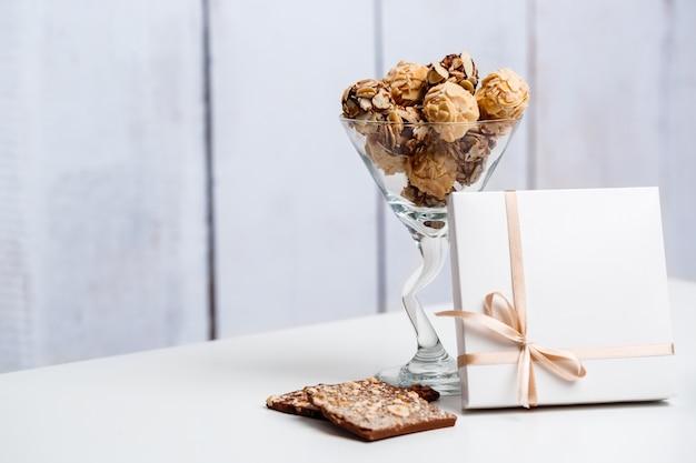 Caramelle di cioccolato in vetro e scatola su bianco