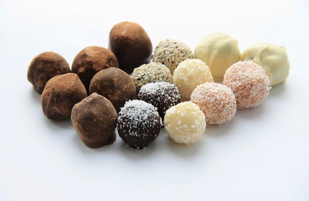 Caramelle di cioccolato rotondi che si spargono su priorità bassa bianca
