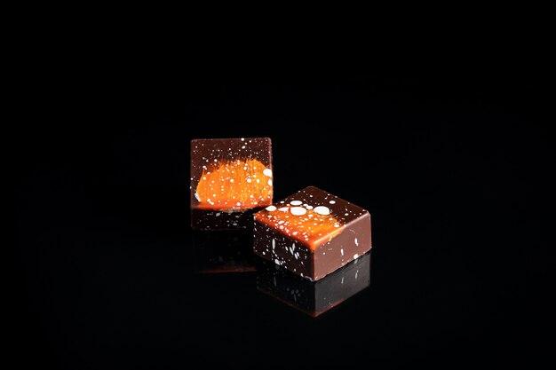 Caramelle di cioccolato variopinte di arte sul fuoco nero e selezionato