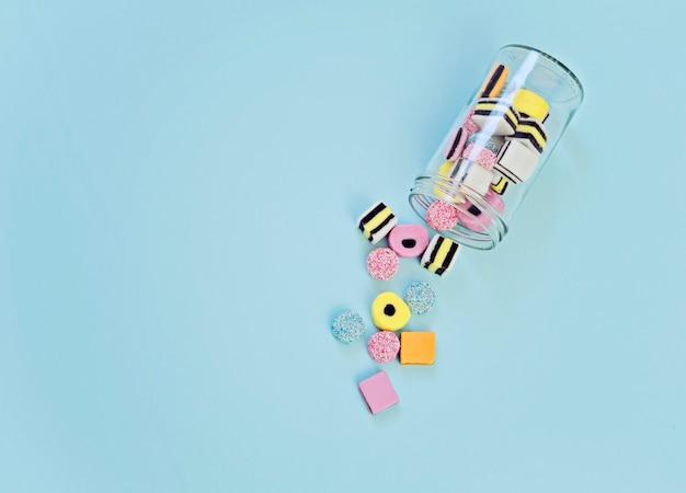 Caramelle di gelatina colorate versate dal barattolo di vetro