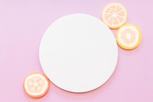 Caramelle di gelatina di zucchero vicino al telaio circolare vuoto bianco su sfondo rosa