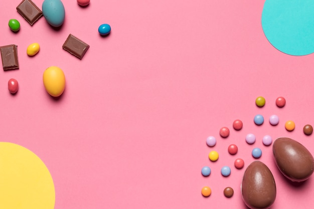 Caramelle di pasqua uova di cioccolato e gemma con lo spazio della copia per la scrittura del testo su sfondo rosa