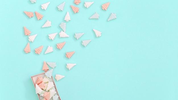 Caramelle dolci, a forma di alberi di natale, sono sparse dalla confezione regalo