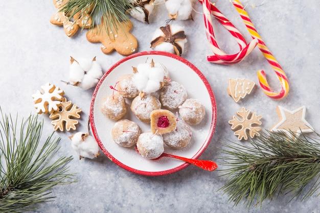 Caramelle dolci di natale sulla tabella del dessert. palline di biscotto con ciliegia - loli pop o cake pop. decorazione del nuovo anno e bevanda al sidro di mele. felice concetto di holidey