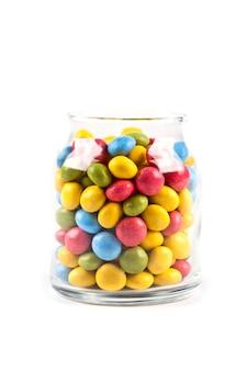 Caramelle dolci variopinte in barattolo di vetro isolato su bianco
