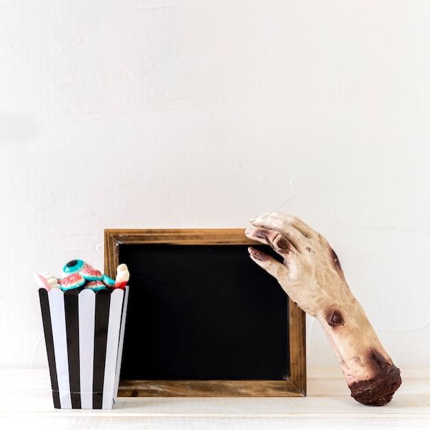 Caramelle e mano zombie vicino alla lavagna
