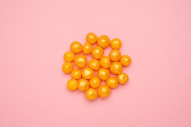 Caramelle gialle dolci su un alimento dolce rosa e rotondo