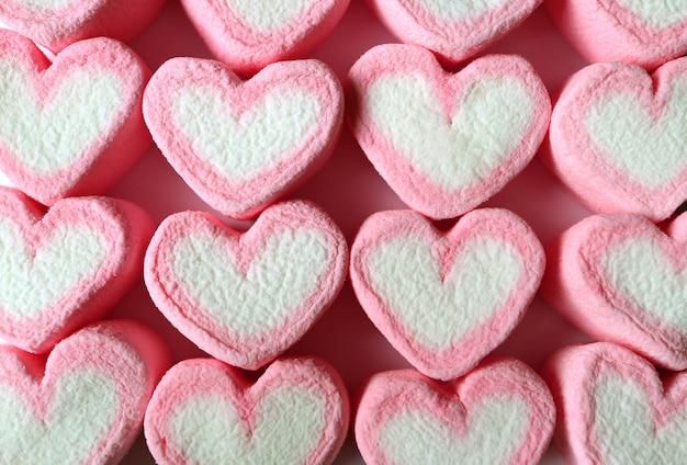 Caramelle gommosa e molle a forma di cuore pastello allineate di rosa e bianco per fondo