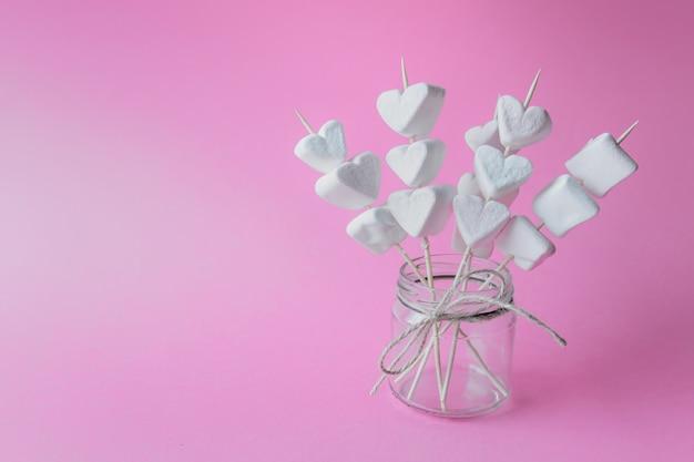 Caramelle gommosa e molle a forma di cuore sui bastoni di legno su fondo di carta rosa in barattolo di vetro