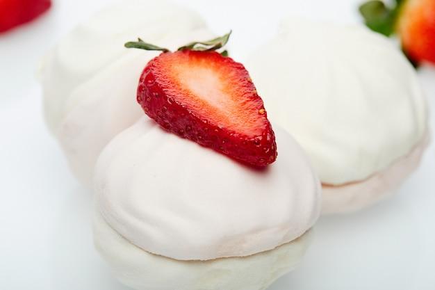 Caramelle gommosa e molle bianche con le fragole fresche su un piatto bianco