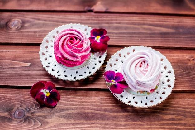 Caramelle gommosa e molle bianche e rosa dello zefiro su di legno.