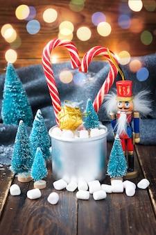 Caramelle gommosa e molle di natale e decorazioni del nuovo anno su legno con il plaid grigio. vacanze invernali