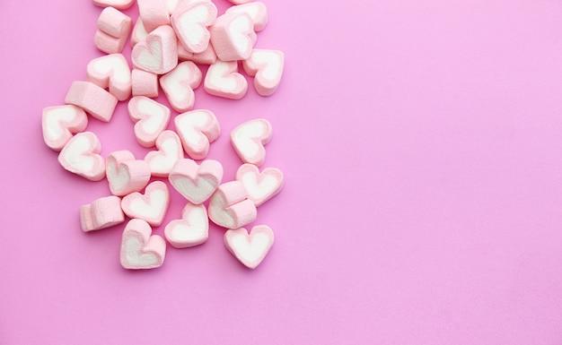 Caramelle gommosa e molle di rosa di vista superiore di progettazione del modello di disposizione piana su fondo dolce con lo spazio della copia