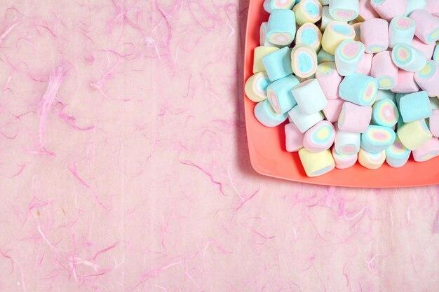 Caramelle gommosa e molle dolci di candy a colori il piatto su fondo rosa