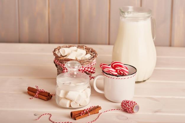Caramelle gommosa e molle, lecca-lecca e latte dei dolci del nuovo anno sulla tavola con i regali