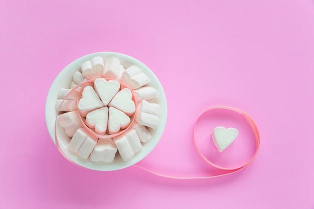 Caramelle gommosa e molle nelle forme del cuore per il giorno di san valentino sopra fondo di carta rosa