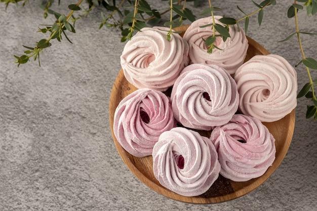 Caramelle gommosa e molle rosa su una tavola grigia