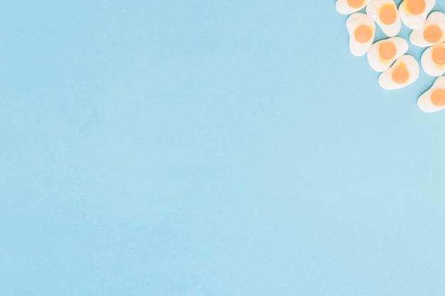 Caramelle gommose fritte dell'uovo sull'angolo di fondo blu