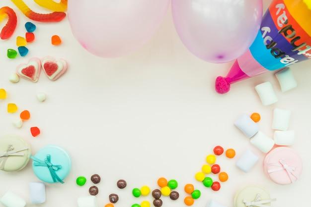 Caramelle; marshmallow; palloncini e cappello di compleanno su sfondo bianco
