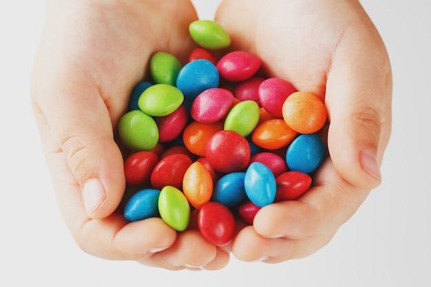 Caramelle multicolori nelle mani di un bambino su uno sfondo bianco