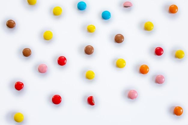 Caramelle rotonde multicolori sparse. modello di confetti al cioccolato in glassa multicolore su sfondo bianco