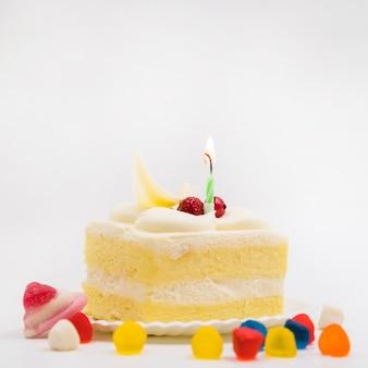 Caramelle variopinte con la fetta di torta sul piatto contro fondo bianco