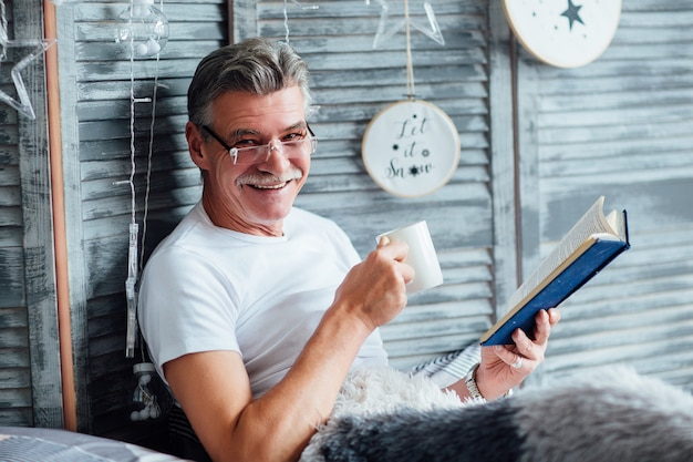 Carattere dell'uomo senior che si trova sul sofà e che legge un libro, anziani che conducono un concetto attivo del sociale di stile di vita.