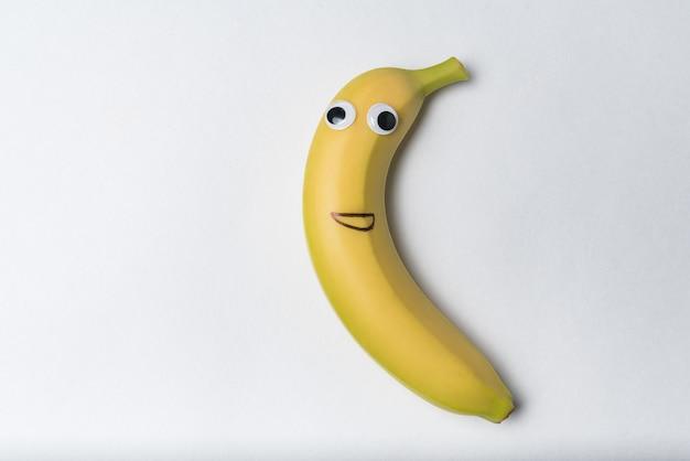 Carattere di banana con la faccia buffa su sfondo bianco. banana con occhi googly e sorriso dipinto