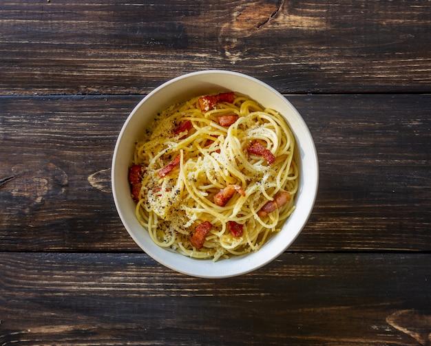 Carbonara degli spaghetti della pasta su una tavola di legno. cucina italiana. ricetta. stile rustico.