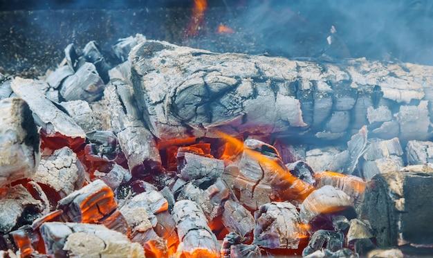 Carbone ardente nel pozzo della griglia del bbq isolato su fondo nero