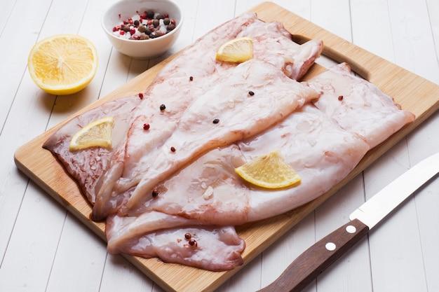 Carcassa di calamari crudi con spezie e limone pronti per la cottura sul tavolo.