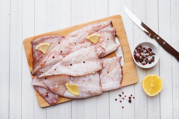 Carcassa di calamaro crudo con spezie e limone pronto per la cottura sul tavolo.