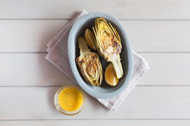 Carciofi e limoni sul piatto. servito con salsa sfondo bianco in legno questo prodotto ha una delle più alte capacità antiossidanti