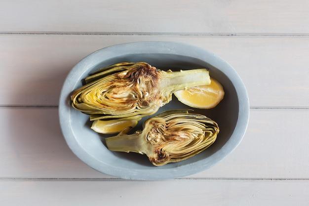 Carciofi e limoni sul piatto. sfondo bianco in legno questo prodotto ha una delle più alte capacità antiossidanti