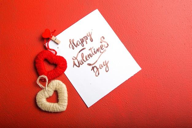 Cardi il messaggio con il giorno di biglietti di s. valentino e il giocattolo felici del cuore sulla tavola rossa