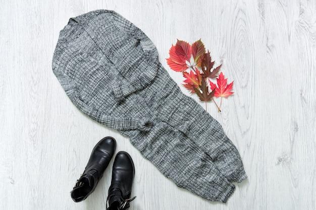 Cardigan lungo grigio, stivali neri e foglie rosse d'autunnali