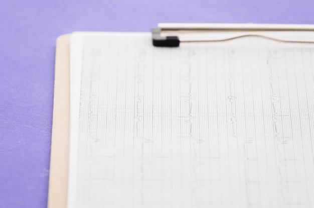 Cardiogramma; grafico ecg su appunti sopra lo sfondo viola