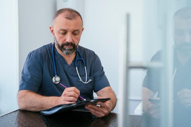Cardiologo professionista che tiene una cartella con lo stetoscopio. primo piano e dettaglio.