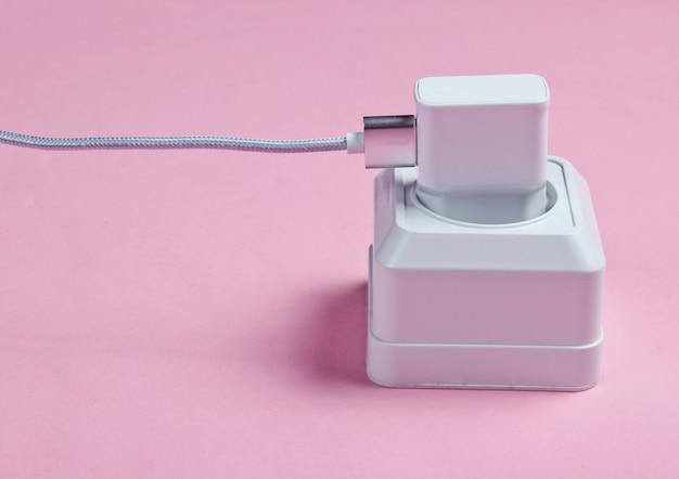 Caricabatterie collegato alla presa di corrente sul tavolo rosa