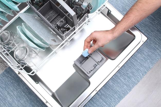 Caricamento del tablet in lavastoviglie. un uomo mette il tablet in lavastoviglie per lavare i piatti sporchi, vista dall'alto