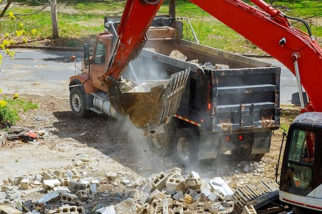 Caricamento della paletta dell'escavatore dell'escavatore a cucchiaia rovescia dalla costruzione nell'autocarro con cassone ribaltabile dei detriti della costruzione