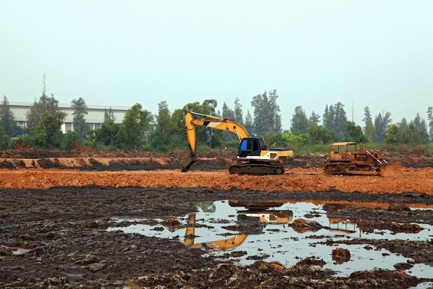 Caricatore dell'escavatore con terna in piedi nella sabbionaia