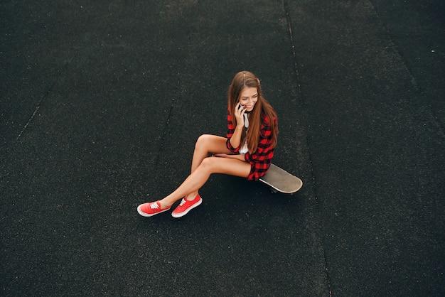 Carina bella giovane donna con un sorriso perfetto in una maglietta bianca, camicia rossa, pantaloncini e scarpe da ginnastica, seduto su uno skateboard