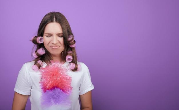 Carina donna dai capelli castani in bigodini non vuole pulire.