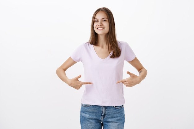 Carina giovane sportiva che dà consigli su come rimanere in forma sorridendo gioiosamente guardando amichevole indicando t-shirt o pancia in piedi deliziata e soddisfatta con sguardo felice oltre il muro grigio