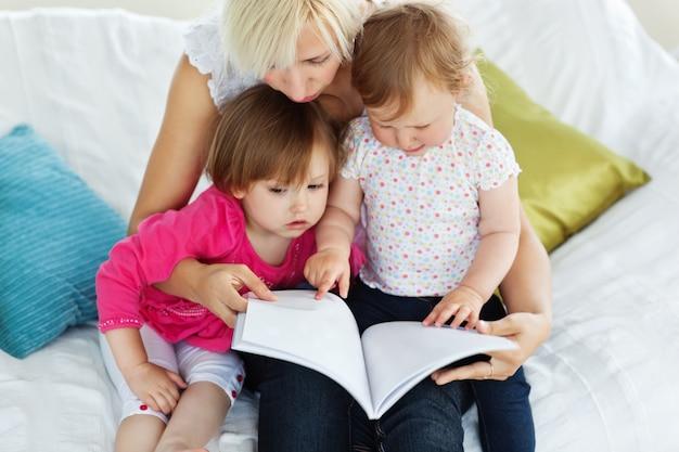 Carina madre leggendo un libro con i bambini