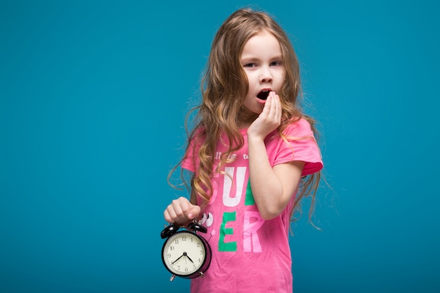 Carina, piccola ragazza in maglietta con i capelli brunet, con l'orologio in mano